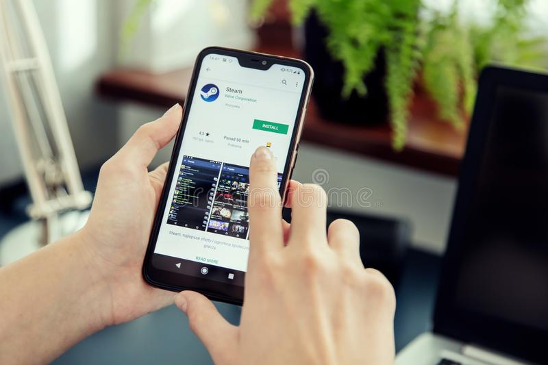 WROCLAW, POLAND - JULY 31th, 2019: Woman installs Netflix application on the Xiaomi A2 smartphone. stock photo
