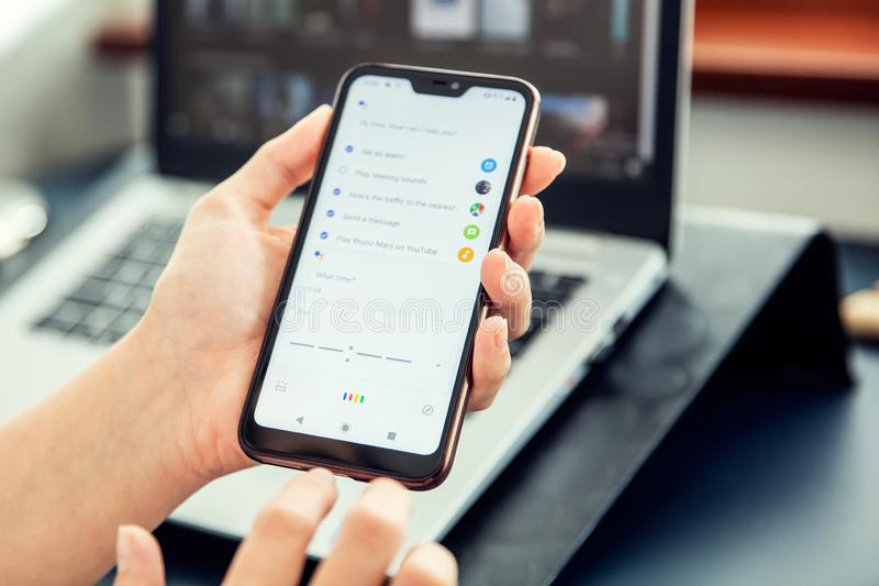 WROCLAW, POLAND - JULY 31th, 2019: Woman uses google assistant on xiaomi a2 smartphone. stock photos