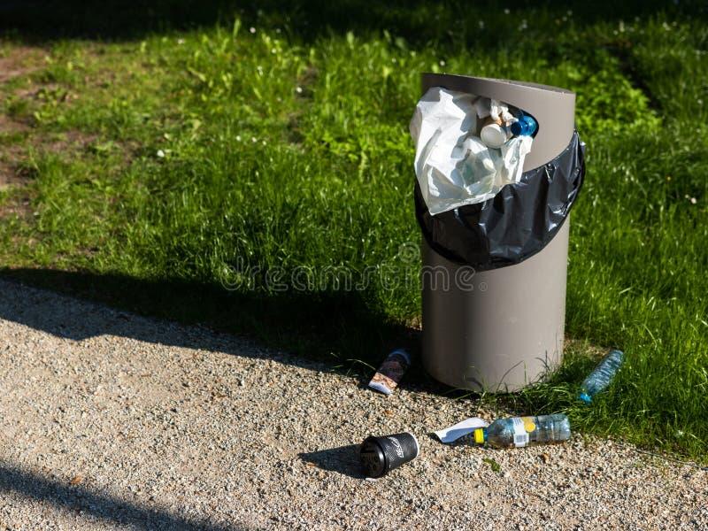 Wroclaw, Polen - Juni 2 2019: Een volledige vuilnisbak Het plastic afval is verspreid op het gras in het openbare park naast Japa stock afbeelding