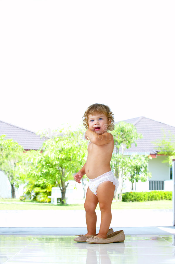 Wrong shoes. High key portrait of baby trying to walk in mama's shoes stock images