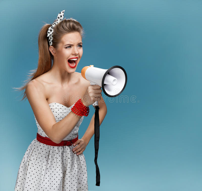 Wroth pin-up girl yells through megaphone, mouthpiece, speaking trumpet. Filmmaking or film production concept. Photo set of young American pin-up model on blue stock photo