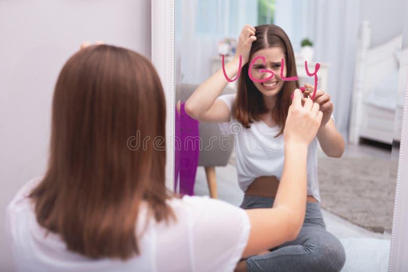 Wroth tienermeisje die als lelijk beschouwen stock afbeelding