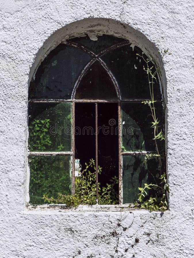 Wrought iron arch window in old church wall. Beautiful old arch window in empty dilapidated church where nature goes its way again stock photo