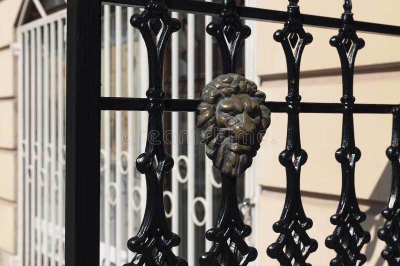 Wrought iron with brass lion`s head. Detail of wrought iron with brass lion`s head stock photos
