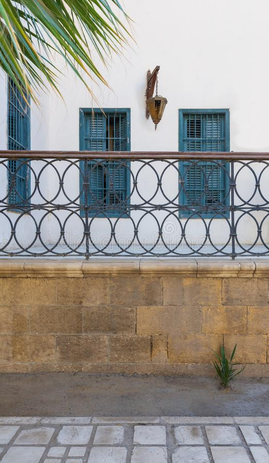 Wrought iron decorative balustrade, and white wall with green window shutters and vintage lantern royalty free stock photo