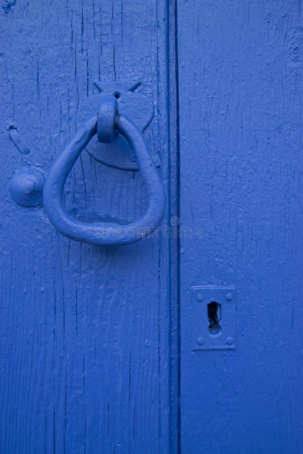 Wrought iron door knob and blue wood door stock images