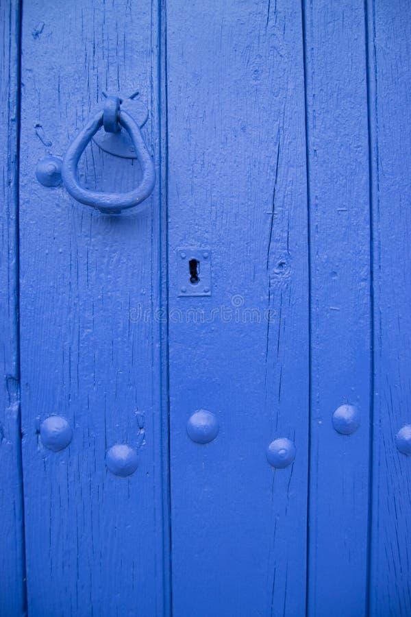 Wrought iron door knob and blue wood door stock image