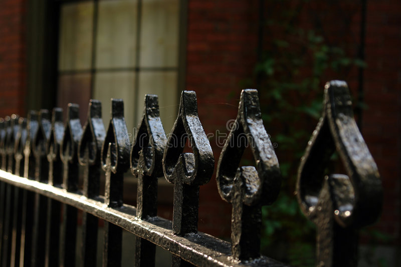 Wrought Iron Fence Of Spades. Black shiny wrought iron fence with tops shaped like spades, shallow depth of field to add a spooky feel to the image, brick royalty free stock photography
