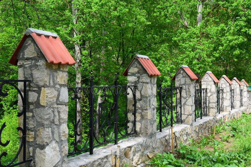 Wrought iron fence with stone columns and caps of tiles stock image