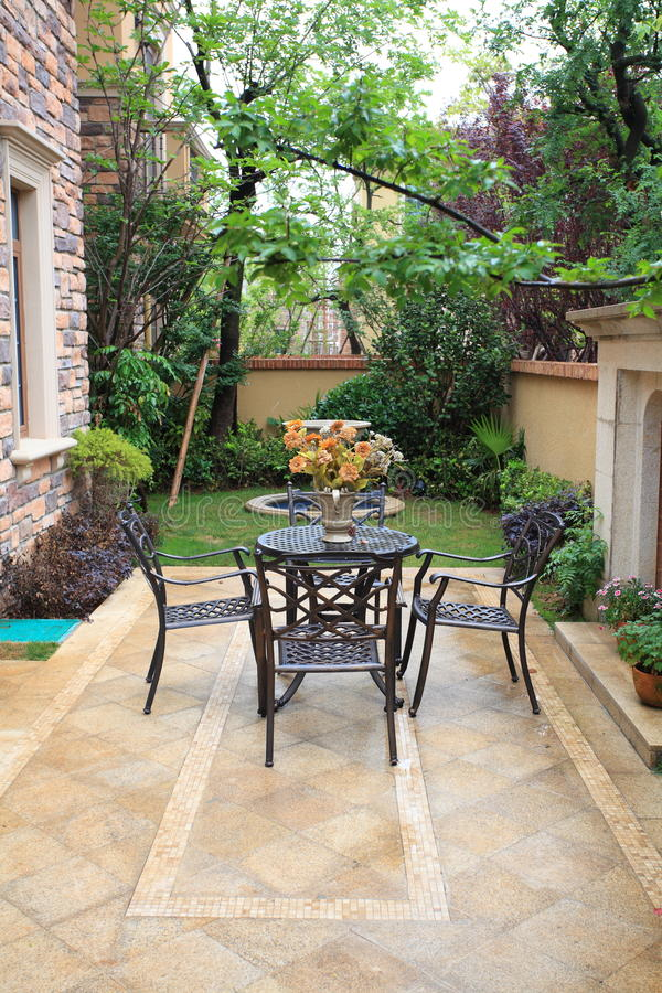 Wrought iron furniture in airy courtyard stock photography