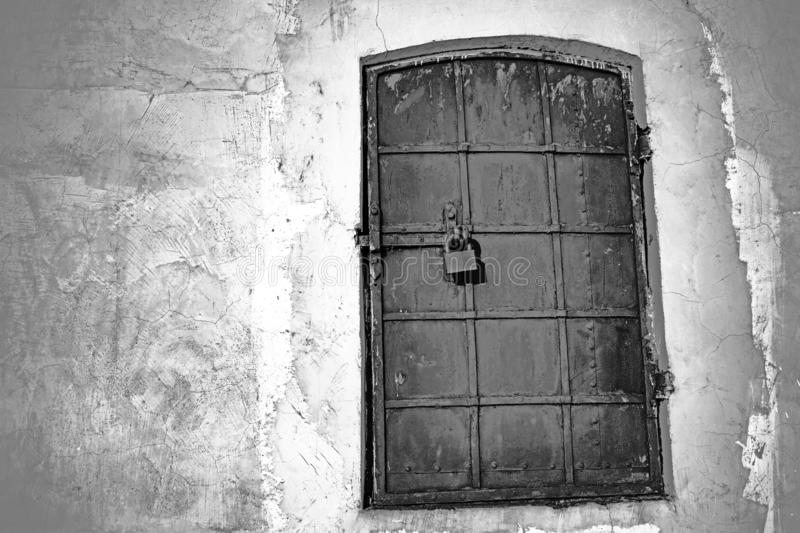 Wrought iron metal door and white wall of an old historic building. Black and white background, retro, vintage stock image