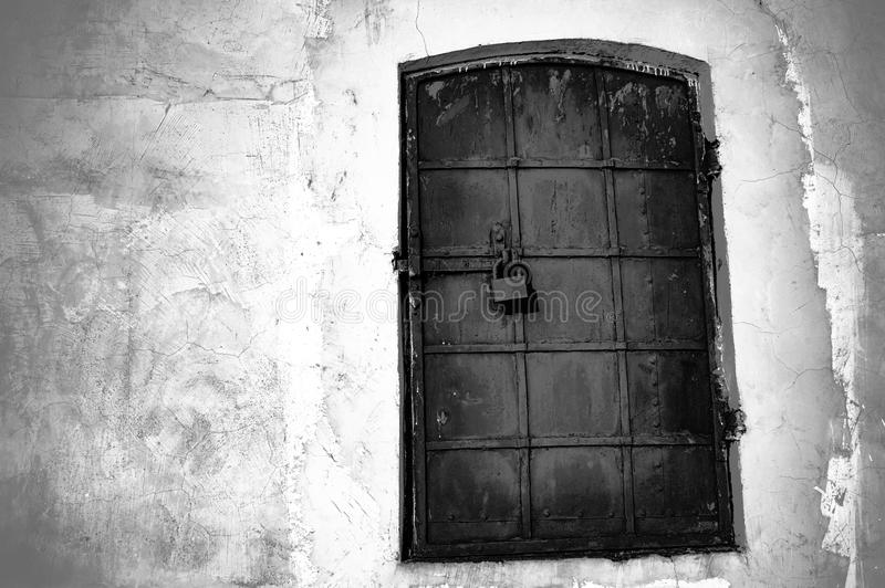 Wrought iron metal door and white wall of an old historic building. Black and white background, retro, vintage stock photos