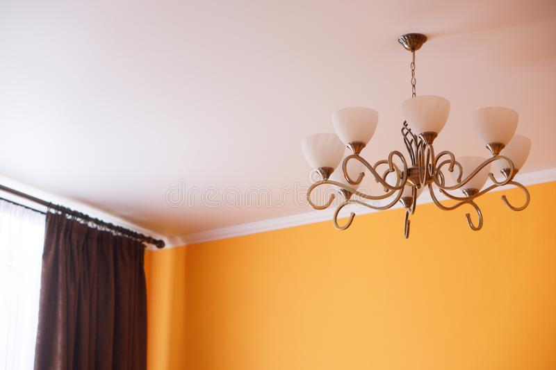 A wrought-iron vintage retro chandelier with eight shades hangs in the room, on the ceiling, not far from the window stock photo