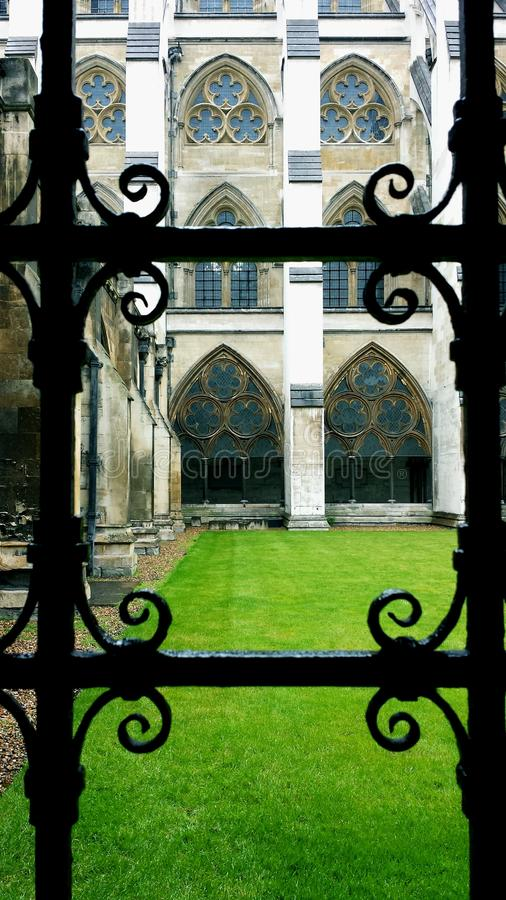 Wrought iron window of ancient church overlooking green grass of courtyard. Wrought iron window of ancient church Westmonster Abbey overlooking green grass of stock images