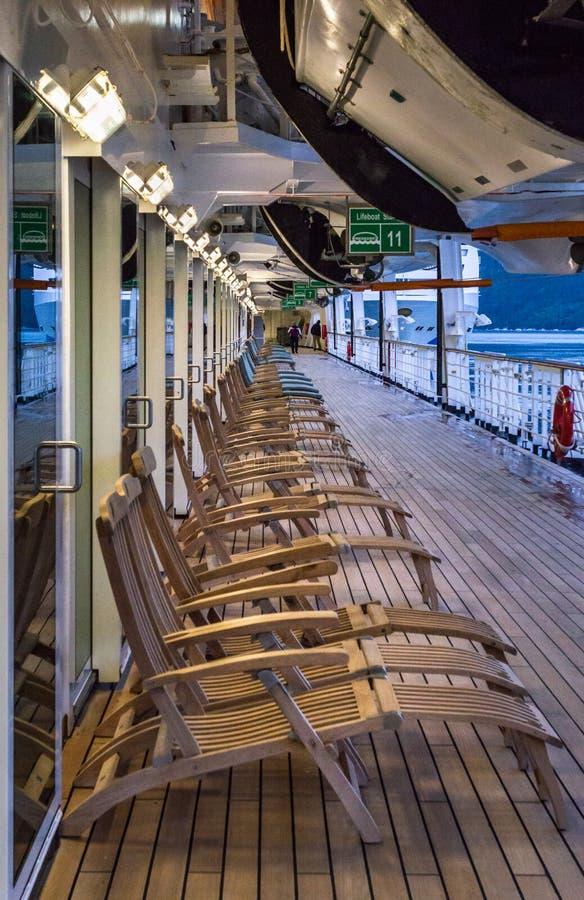 Wrzesień 15, 2018 - Skagway, AK: Rząd statku wycieczkowego pokładu drewniani krzesła, wczesny poranek zdjęcie royalty free