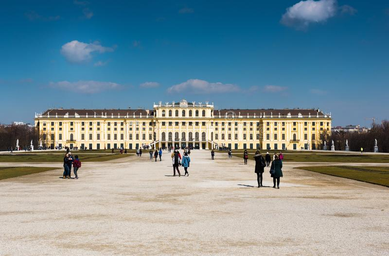 Schönbrunn Palace with tourists. WS View of Schönbrunn Palace in Vienna Austria. Winter time, tourists in shot. Clear blue sky, palace in the background royalty free stock image