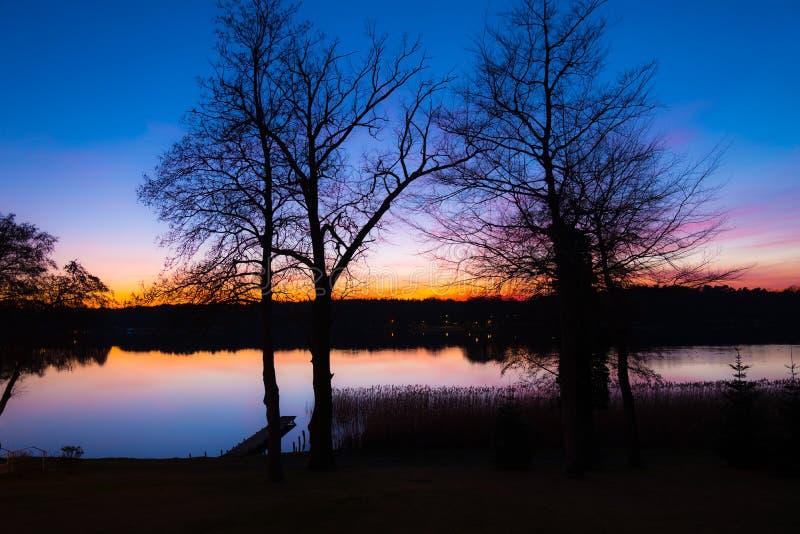 Wschód słońca krajobraz na jeziorze w zimie, z drzewami bezlistnymi - niebo odbija w wodzie obraz stock