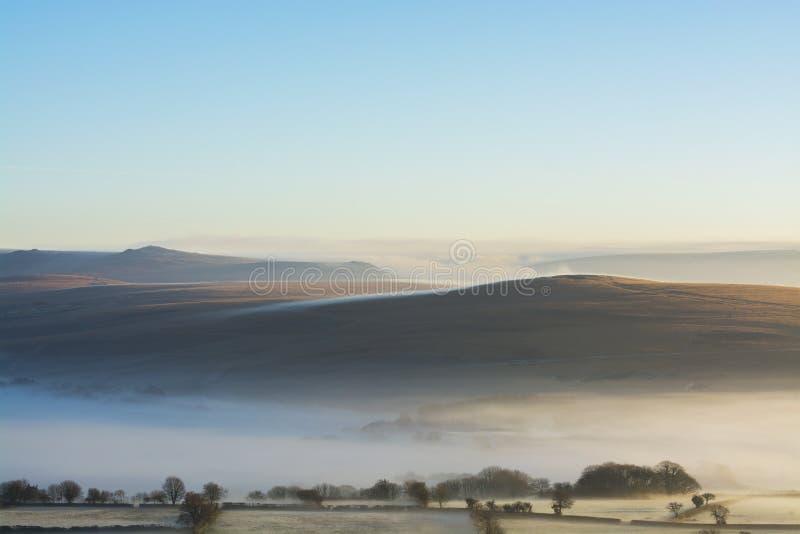 wschód słońca nad Dartmoor z Tors w widoku i mgłą stacza się nad wzgórzami obraz stock