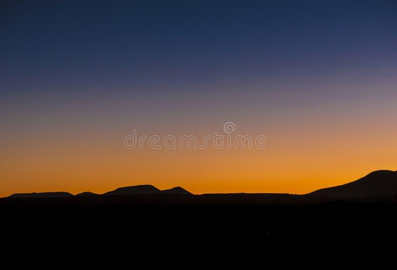Wschód słońca nad deserem z czarnymi sylwetkami halne akademie królewskie zdjęcia stock