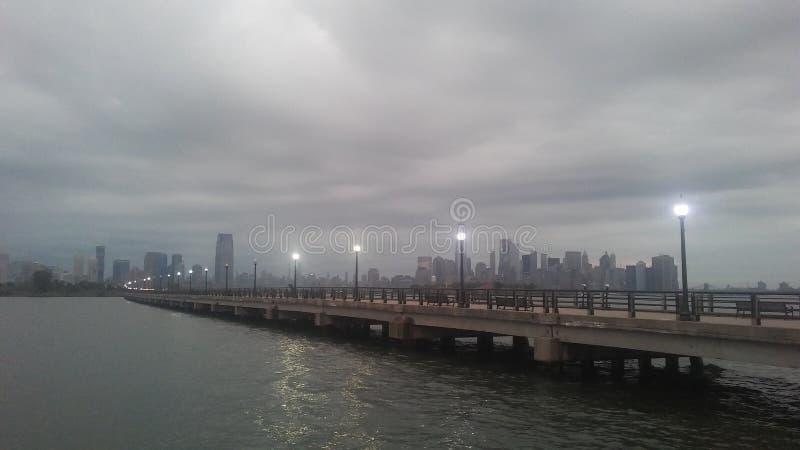 Wschód słońca nad Ellis wyspa i Manhattan na Dżdżystym Chmurnym ranku w lecie obraz royalty free