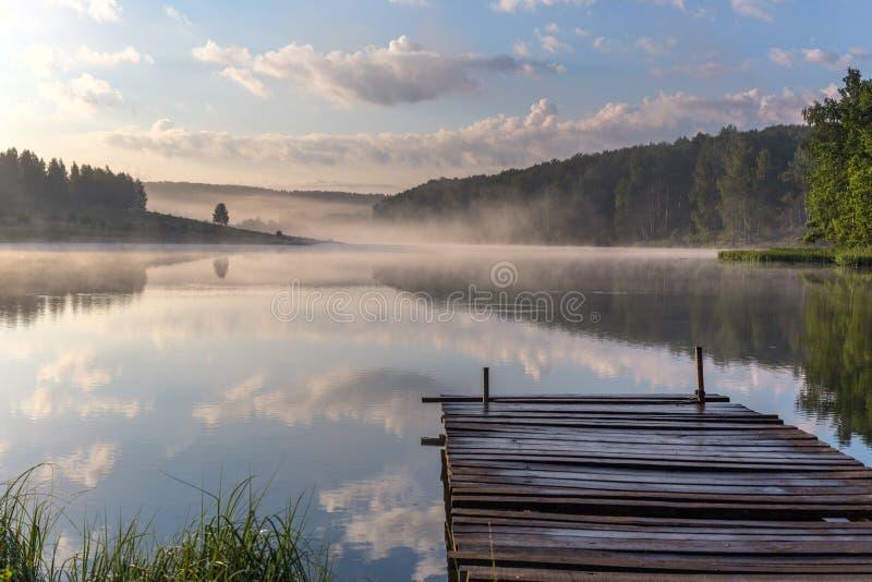 Wschód słońca nad mgłową rzeką z drewnianym molem zdjęcie stock