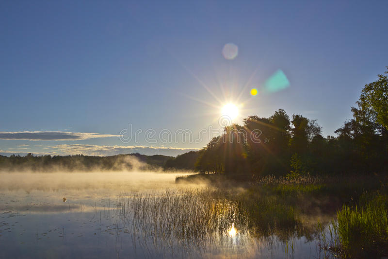 Wschód słońca nad mgłowym jeziorem obraz royalty free
