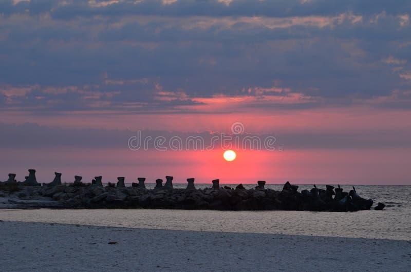 Wschód słońca nad morze plażą, kamienny jetty fotografia royalty free