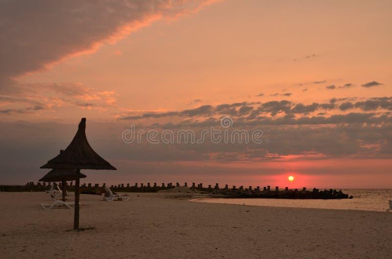 Wschód słońca nad morze plażą, trzcinowi parasole, krajobraz zdjęcia royalty free