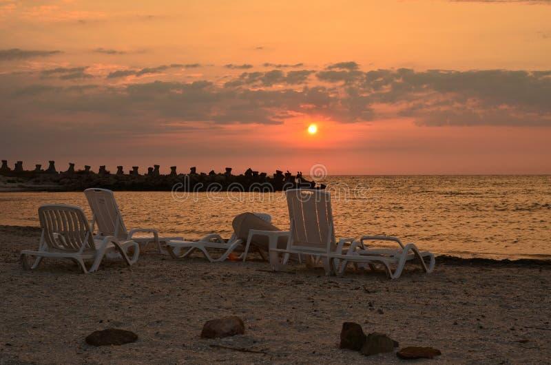 Wschód słońca nad morze plażą z pokładów krzesłami zdjęcia royalty free