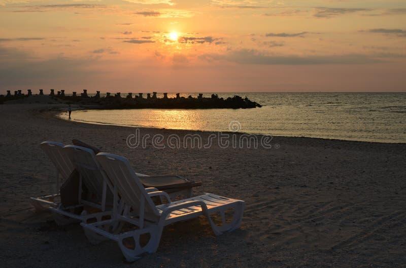 Wschód słońca nad morze plażą z pokładów krzesłami zdjęcia stock