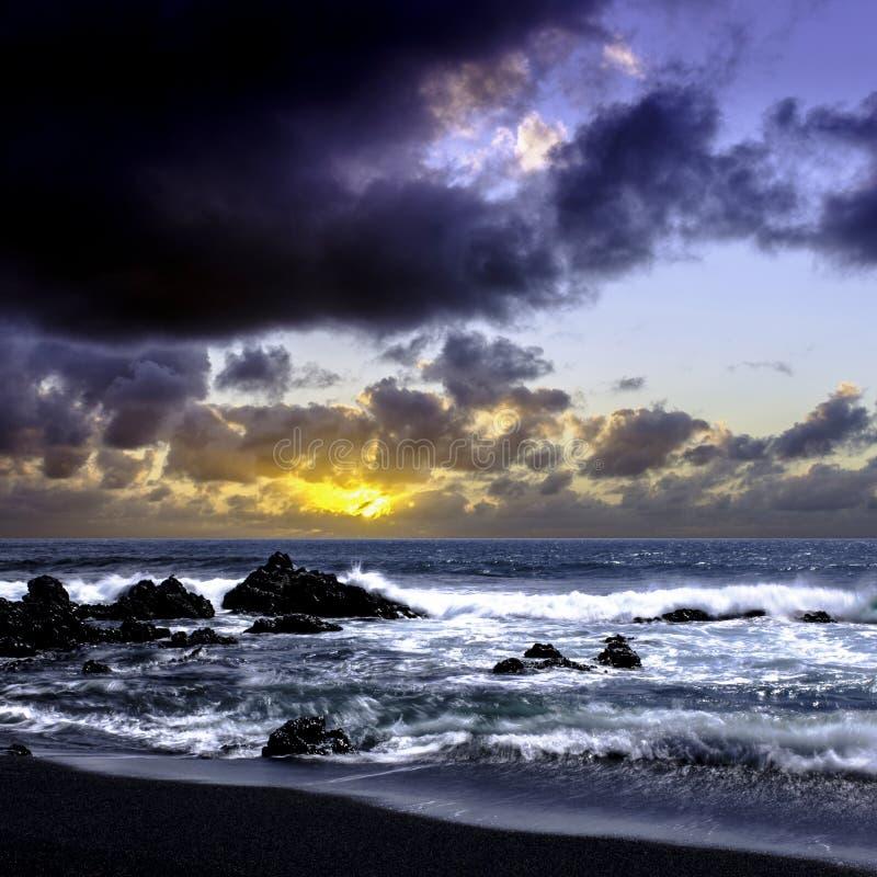 Wschód słońca nad oceanem zanim burza - czarny powulkaniczny plażowy pobliski El Golfo, Lanzarote zdjęcia stock