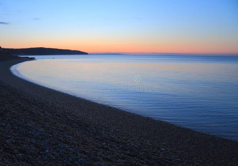 Wschód słońca nad otoczak plażą obrazy stock