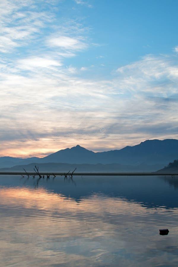 Wschód słońca nad stronniczo zanurzać nieżywymi gałąź w Jeziornym Isabella w sierra Nevada góry w środkowym Kalifornia usa obraz stock