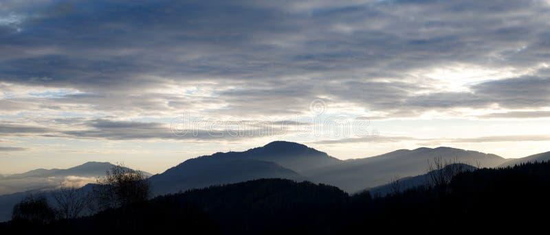 Wschód słońca w austriackich alps błyszczy przy mistyczką chmurnieje w górę sypialnych szczytów w Styria obrazy royalty free