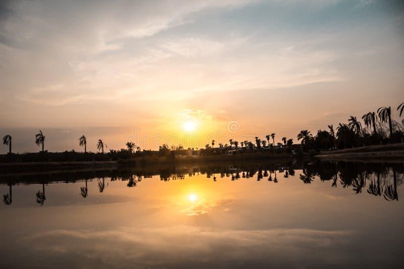 Wschód słońca z odbiciem drzewka palmowe i miastem w zaciszności wodzie obraz stock