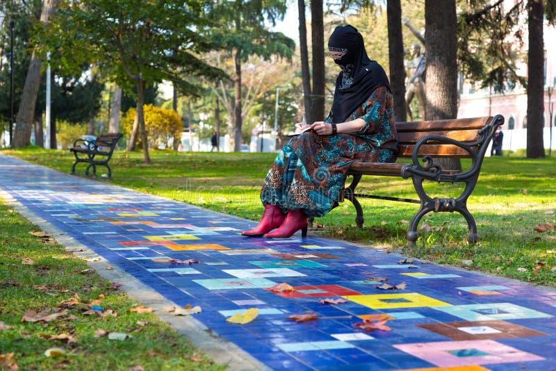 Wschodni kobiety obsiadanie na ławce przy colourful Parkową aleją obrazy stock