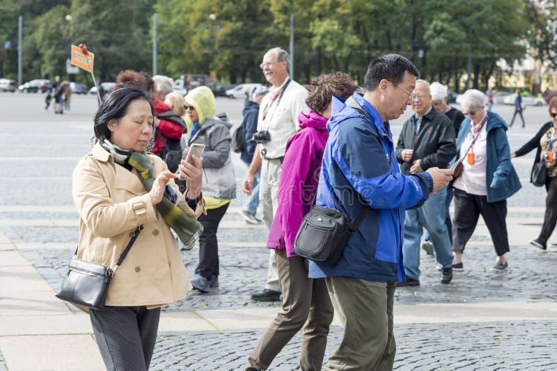 Wschodni turyści mężczyzna i kobieta iść na wiszących ozdób gps trasie St Petersburg, Rosja, Wrzesień, 2018 zdjęcia royalty free