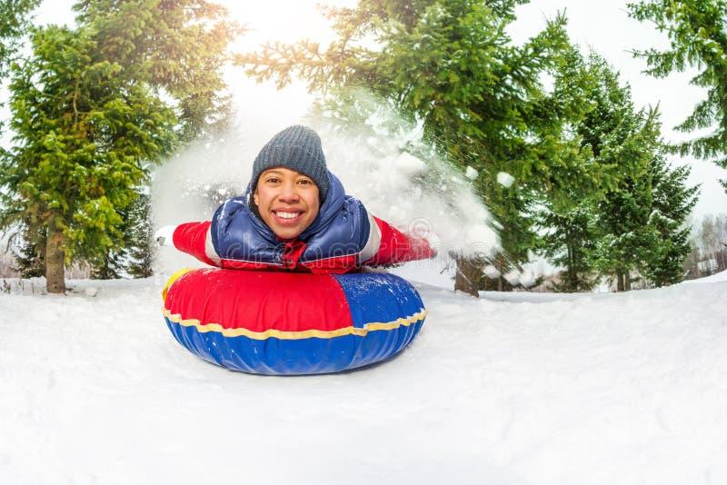 Wschodnio-azjatycki chłopiec na śnieżnej tubce w zimie samotnie obraz royalty free