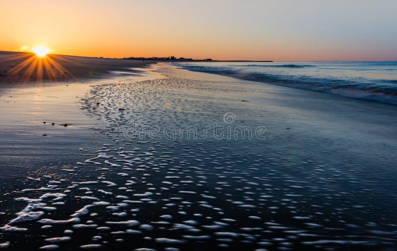 Wschodu słońca starburst przy przylądkiem Maj, NJ, plaża jako niski przypływ płynie przez piasek zdjęcia royalty free