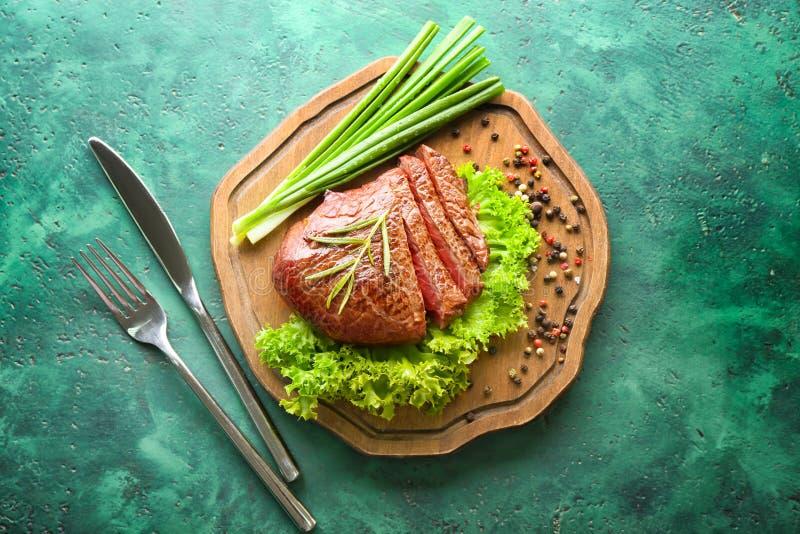 Wsiada z smakowitym rżniętym stkiem, ziele, zieloną cebulą i pikantność na zielonym tle, zdjęcie royalty free
