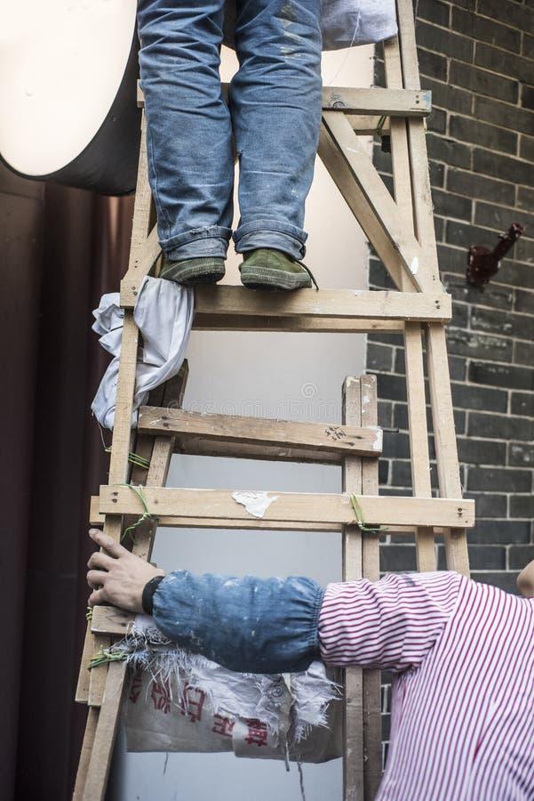 Współpraca, ręka naciera drewnianą drabinę, nożna pozycja na drewnianej drabinie, zdjęcia stock
