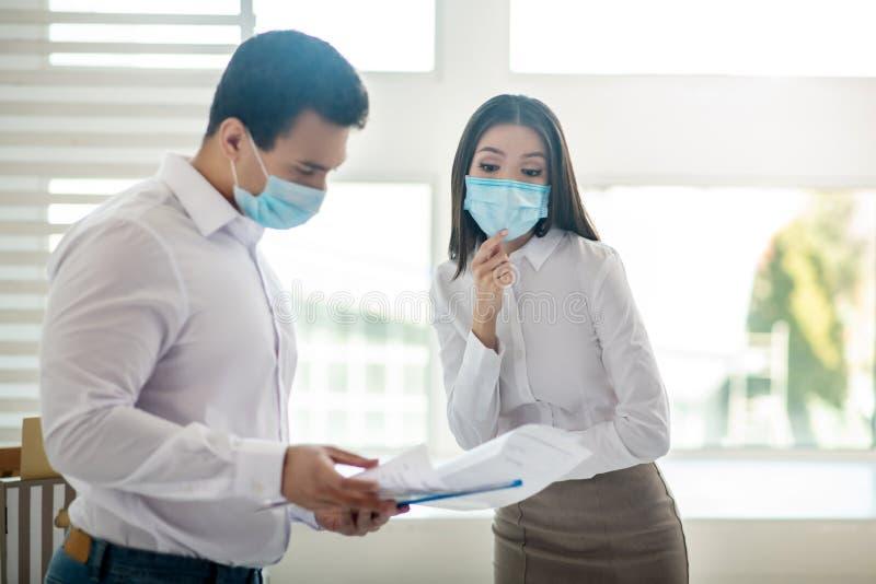 Współpracujący w biurze współpracownicy w maskach ochronnych obraz stock