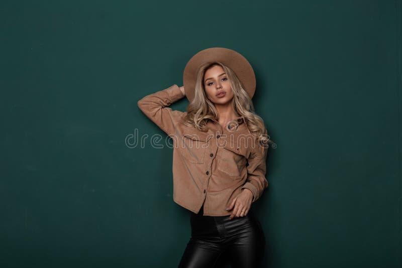 Wspaniała młoda kobieta z blondynem w eleganckim kapeluszu w eleganckiej beżowej koszula w rzemiennym czerni dyszy w retro stylow fotografia royalty free