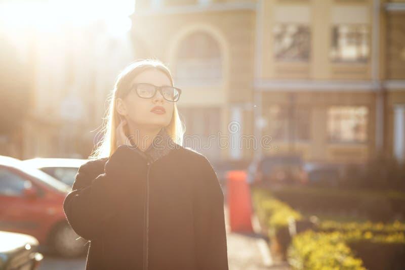 Wspaniały blondynka model jest ubranym szkła i odprowadzenie puszka pogodną ulicę Opróżnia przestrzeń obrazy stock