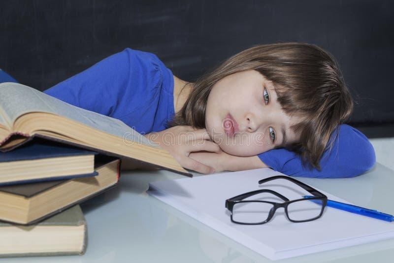 Wspaniały młody pracowity uczeń studiujący męczył wśród jego książek podczas gdy zdjęcia stock
