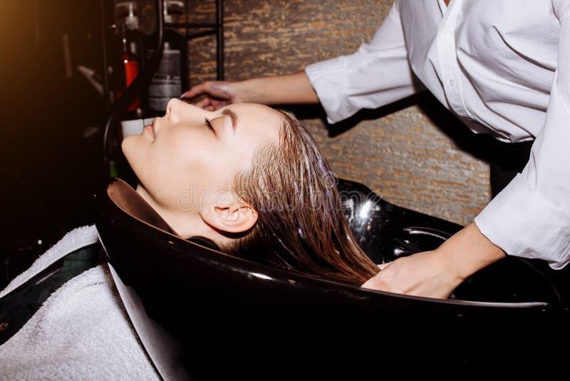 Wspaniała śliczna młoda kobieta cieszy się kierowniczego masaż podczas gdy fachowy fryzjer stosuje szampon jej włosy Zamyka w gór obrazy royalty free