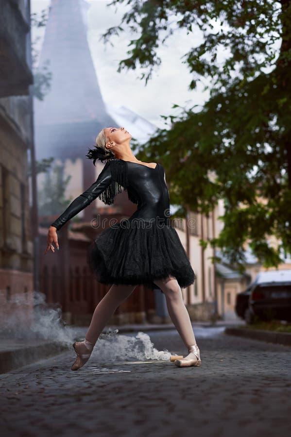Wspaniała balerina w czarnym stroju tanu w miasto ulicach fotografia stock