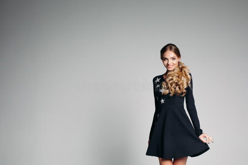 Wspaniała blondynki dziewczyna z kędzierzawym włosy w czarnej mini sukni z srebnymi gwiazdami zdjęcia stock
