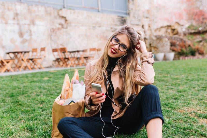 Wspaniała blondynki dziewczyna z piekarni torby obsiadaniem na trawie przed starym budynkiem i słuchającą muzyką Elegancka kobiet zdjęcia royalty free