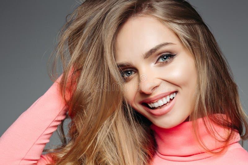Wspaniała blondynki kobieta w różowym pulowerze z falistym volumed włosy obraz stock